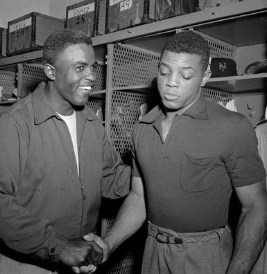 Jackie Robinson of the Brooklyn Dodgers (L) congratulates New York Giant Willie Mays, after the Giants beat the Dodgers 7 to 1, capturing the 1954 National League pennant.  (American Academy of Achievement)