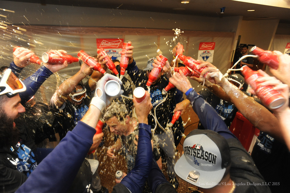 Andrew Friedman gets a champagne bath after the clinch Tuesday.