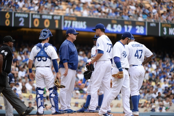 Pitching coach Rick Honeycutt visits Carlos Frias at the mound during a May 24 game. (Jill Weisleder/Los Angeles Dodgers)