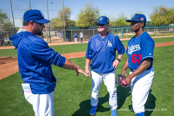 Eric Gagne and Rick Honeycutt talk with Jharel Cotton on February 28.