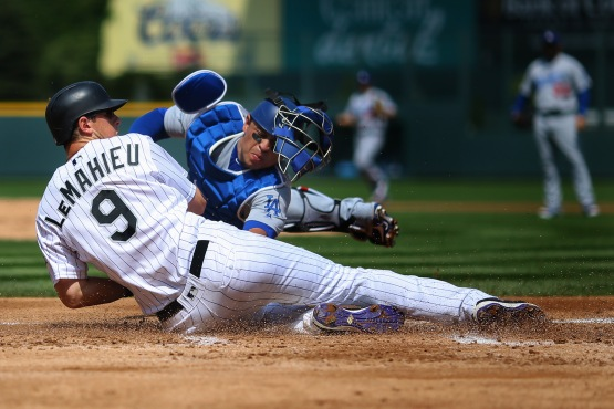 DJ LeMahieu slides ahead of the tag from catcher Carlos Ruiz on a double off the bat of Nolan Arenado in the first inning at Coors Field. (Justin Edmonds/Getty Images)