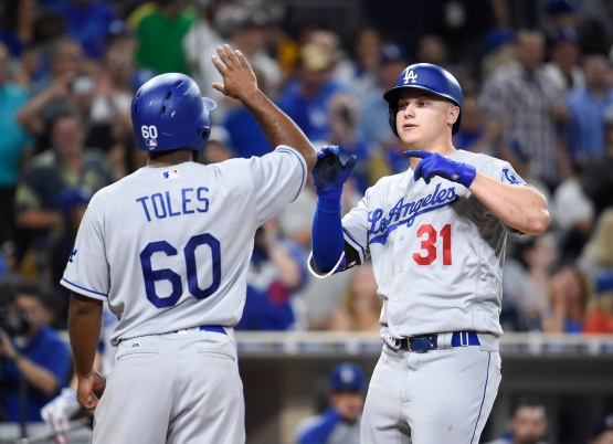 Andrew Toles congratulates Joc Pederson on his 25th homer of the year. (Denis Poroy/Getty Images)